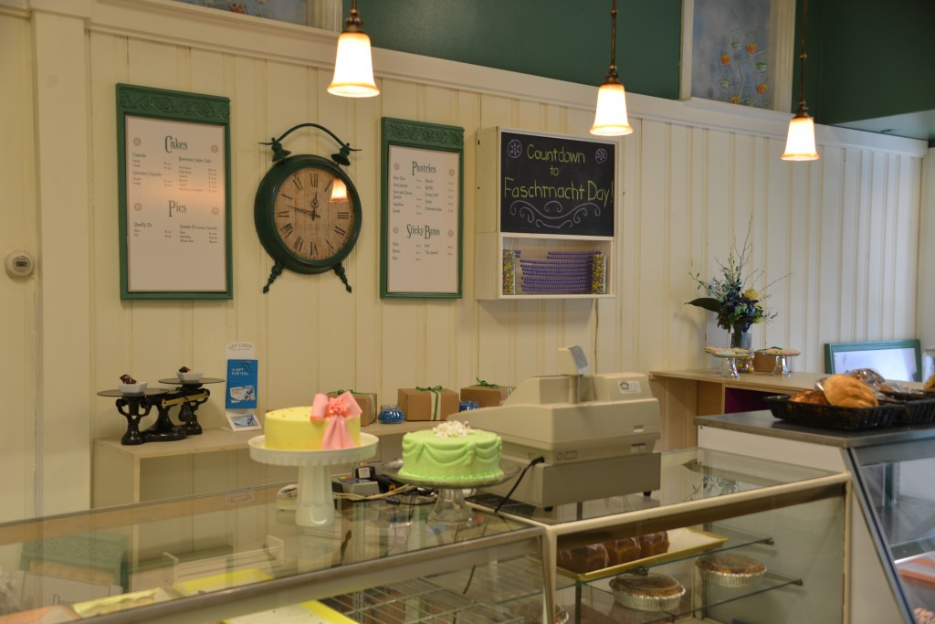 Save My Bakery AFTER: Schubert's Bakery is detailed with new menus, wall art, and display pedestals to show off the new cake designs.
