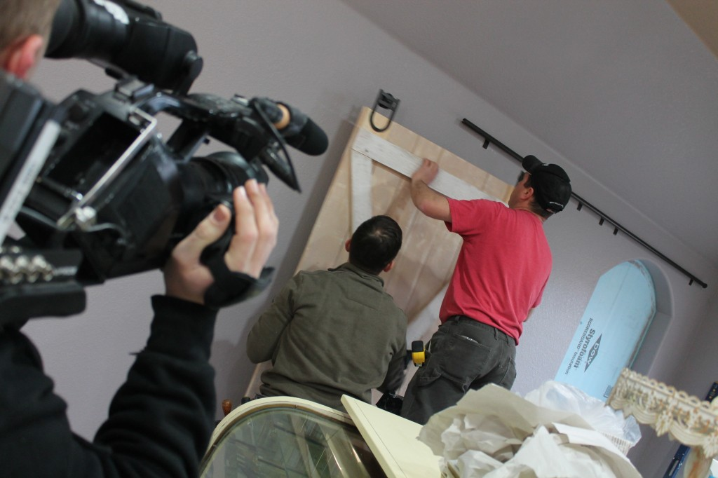 Andy and Matthias install the barn door that Andy made to separate the showroom from the prep room.