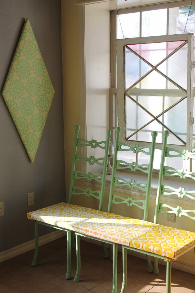 We made a new bench from three of the chairs, and used salvage window to create stained glass window art. Diamond pattern is also seen in the wallpaper covered shapes on the walls.
