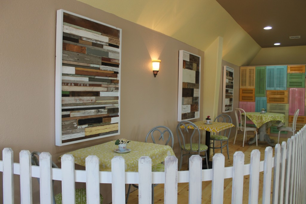 Picket fence with the salvage wood wall art and salvage shutters on a pine floor platform create a fun and more intimate dining experience at Lori's.