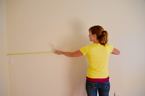 Theresa taking measurements for the wainscoting and chair rail for this girl's bedroom
