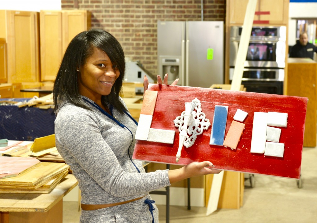 Jessica Massaquoi made this Love wall art with a wall sconce and tile at the Habitat for Humanity ReStore workshop.