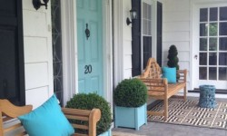 The black-white-and-wood porch might make most select a black or wood door. The aqua blue front door gives personality about the creamy white siding and black accents.