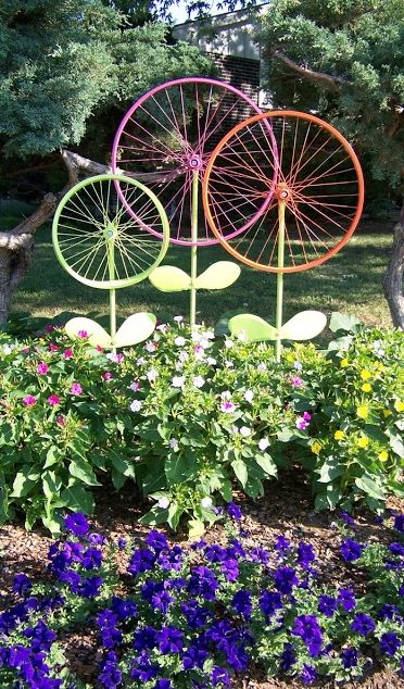 Old bicycle tires painted vibrant colors adds such a charming element to a garden.